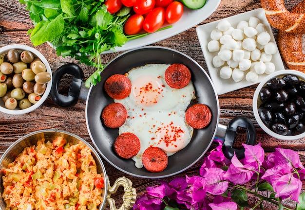 Вид сбоку вкусные блюда в сковороде с салатом, солеными огурцами, цветами на деревянной поверхности