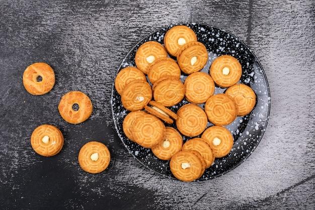 Сахарное печенье в тарелке на темной поверхности