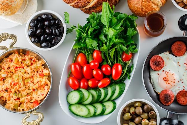 Вид сверху вкусные блюда на сковороде с салатом, солеными огурцами, турецким бубликом, чашкой чая на белой поверхности