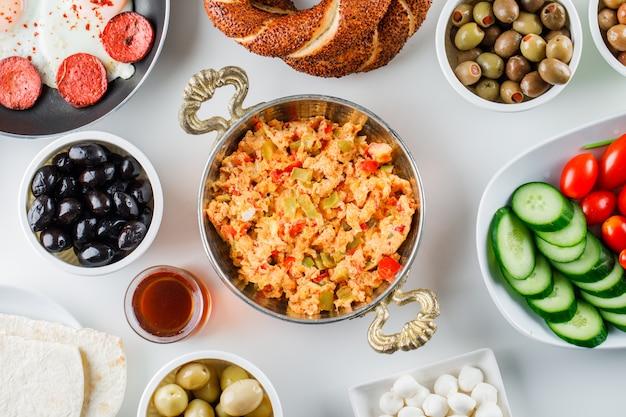 Вид сверху вкусные блюда в сковороде с салатом, солеными огурцами, турецким бубликом на белой поверхности