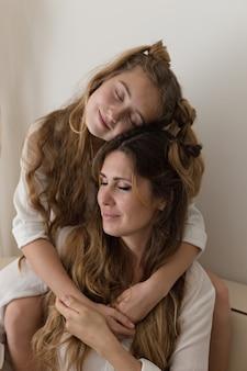 Красивая девушка, обнимая ее мать в гостиной в белой рубашке.