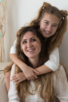 Красивая девушка в белой рубашке сидит и улыбается в гостиной.