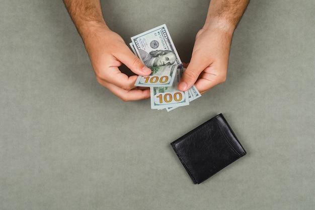 平らな灰色の表面に財布のビジネスと会計の概念を置きます。男はお金を数えます。
