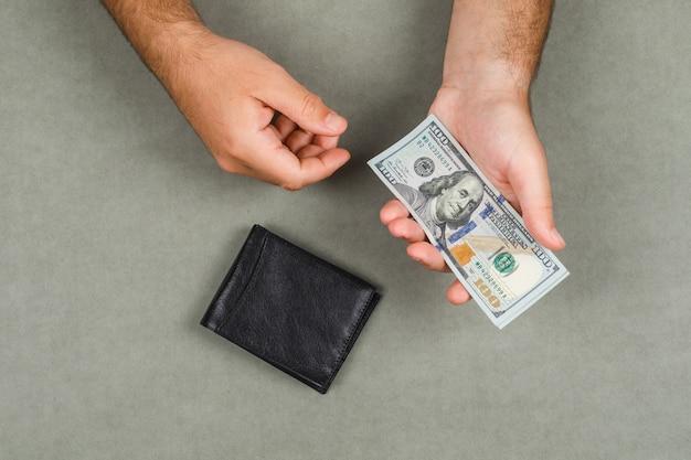 平らな灰色の表面に財布のビジネスと会計の概念を置きます。男はお金を保持しています。