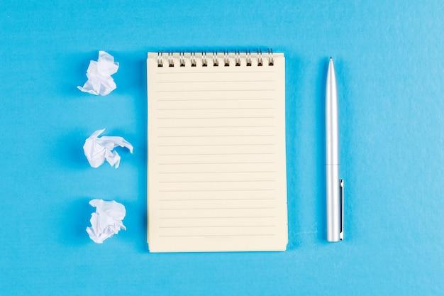 しわくちゃの紙の塊、スパイラルノート、平らな青色の背景にペンでビジネスと金融のコンセプトを置きます。