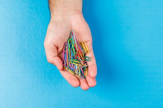 青色の背景に手のひらにペーパークリップでビジネスと金融の概念は横たわっていた。