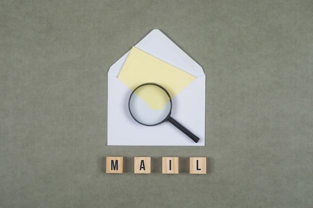 封筒、虫眼鏡、平らな灰色の表面に木製キューブの手紙のビジネスコンセプトを置きます。