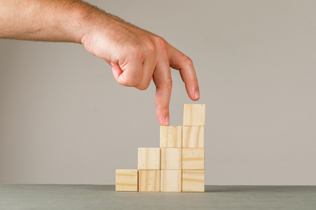 灰色と白の壁の側面図のビジネス成長の概念。階段に指を入れて男。
