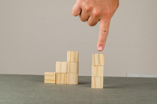 灰色と白の壁の側面にビジネス戦略の概念。男は木製のブロックタワーを示します。