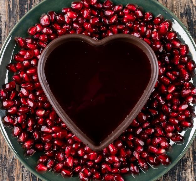 Вид сверху граната в тарелке с тарелкой в форме сердца на деревянной поверхности