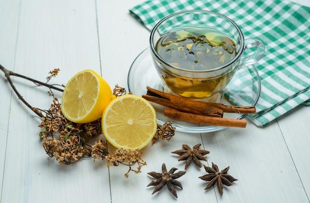 Травяной чай с высушенными травами, специями, ручками циннамона, лимоном в чашке на деревянном и взгляде высокого угла полотенца для чайной посуды.