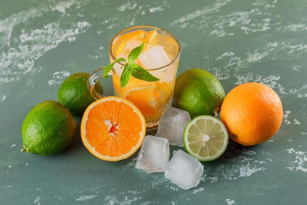 石膏の表面にオレンジ、ミント、ライムのハイアングルとカップの氷のようなデトックス水