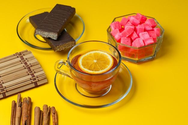 Лимонный чай в чашке со специями, печеньем, кусочками сахара, столовым прибором под большим углом на желтой поверхности