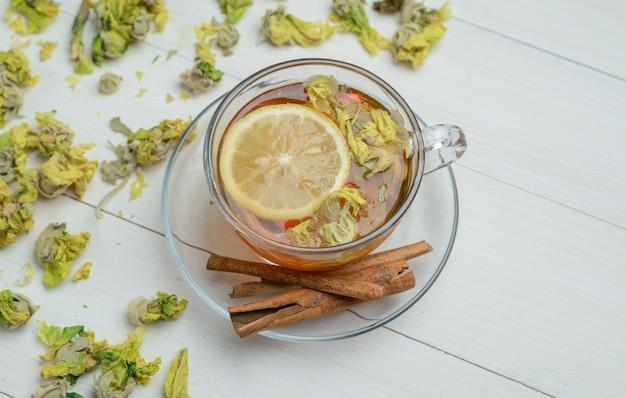 Чай лимона с высушенными травами, ручками циннамона в чашке на деревянной поверхности, взгляде высокого угла.