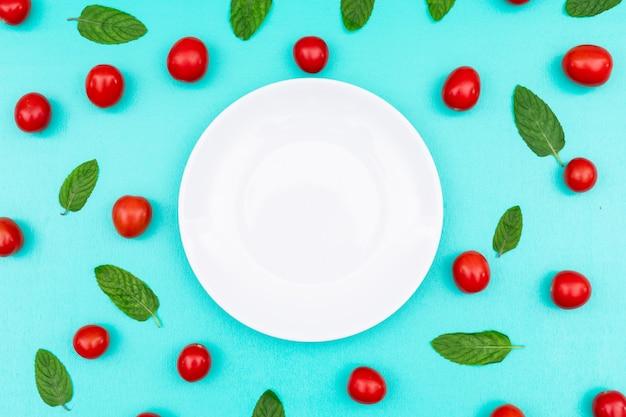 Белая тарелка в окружении красной вишни и мяты сверху на синей поверхности