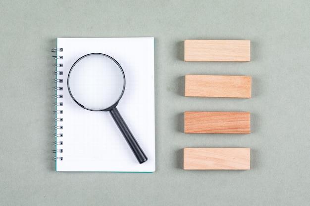 ノートブック、拡大鏡、灰色の背景の上面に木製のブロックの検索と研究のコンセプト。横長画像