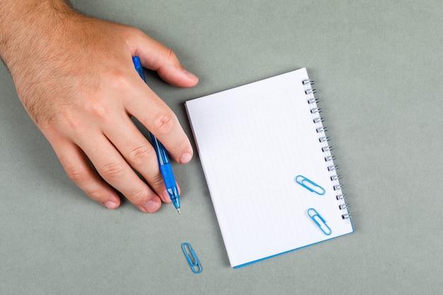 メモを取り、灰色の背景の上面にノートブックで思考の概念。手はペンを保持しています。横長画像