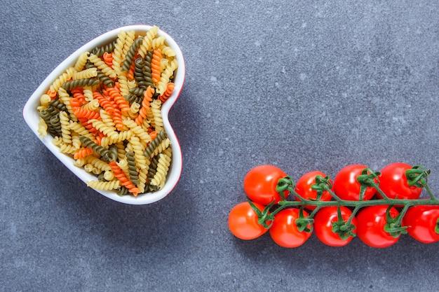 灰色の表面にハート型のボウルにトマトとカラフルなマカロニパスタのセット。上面図。テキストのためのスペース