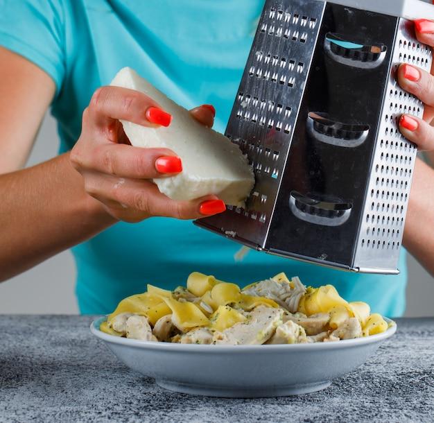 パスタの食事にチーズをすりおろす女性