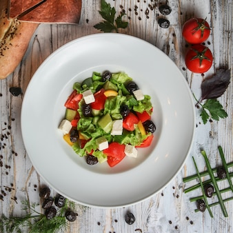 トマト、オリーブ、パン、ハーブ、スパイスとプレートのギリシャ風サラダ