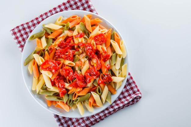 Паста пенне с помидорами, соусом в тарелке на белом и кухонным полотенцем