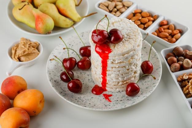 Рисовые лепешки в тарелке с вишней, орехами, грушей, абрикосами, арахисовым маслом