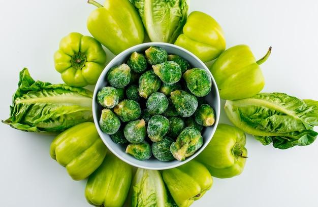 Брюссельская капуста в миску с листьями салата, сладкий перец на белом столе