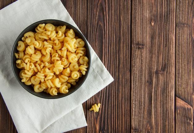 Сухие макароны в миску на фоне деревянных и кухонное полотенце. плоская планировка