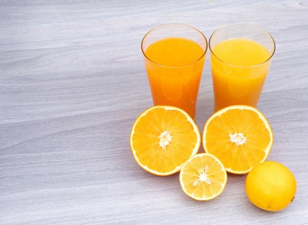 Стакан апельсинового и лимонного сока на белом деревянном столе