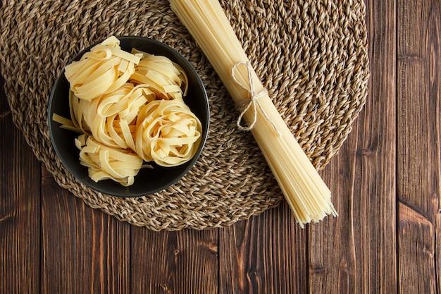 Сырые спагетти с плоской пастой феттучини лежат на деревянном и плетеном фоне столовых приборов