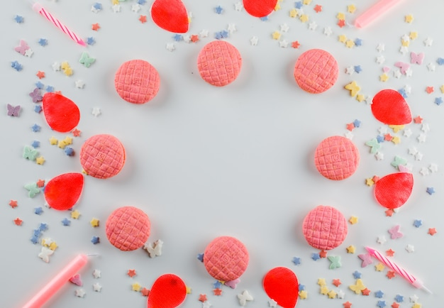 砂糖を振りかける、キャンドル、白いテーブルの上に花びらのクッキー