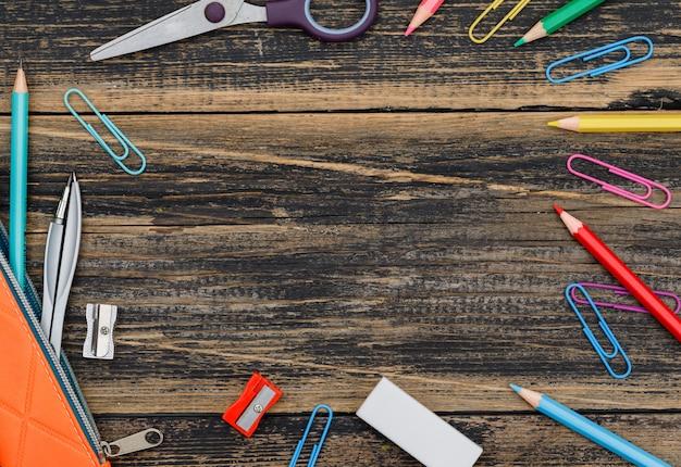 Концепция школы с ассорти школьных принадлежностей на деревянном столе плоской планировки.
