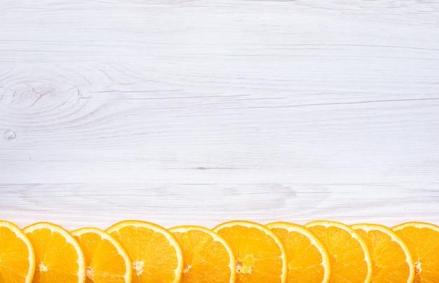 木製の表面にコピースペースを持つ新鮮なオレンジ色の果物トップビューをスライス