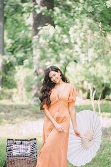 Портрет милой дамы на природе держа зонтик и усмехаясь в оранжевом платье во время дневного времени.