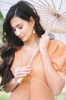 Портрет милой дамы на природе держа зонтик в оранжевом платье во время дневного времени.