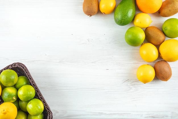 白いテーブルの上のコピースペース付きバスケットで平面図柑橘系の果物