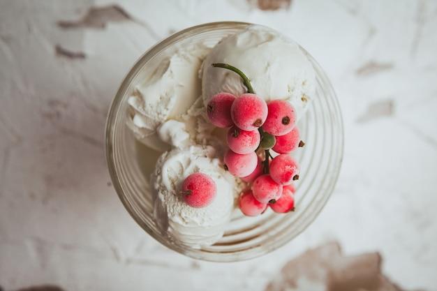 Клюква и мороженое в стеклянной чашке сверху на белом текстурированные