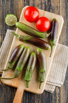 Баклажаны с помидорами, лайм на разделочную доску на деревянные и кухонное полотенце, плоская планировка.