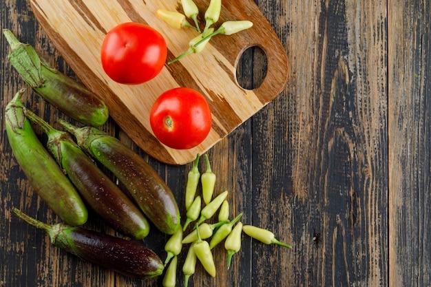 Баклажаны с помидорами, перцем на деревянной и разделочной доске, плоской заложить.