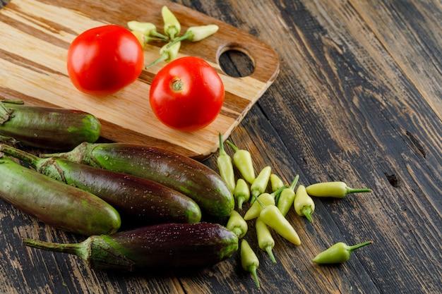 Баклажаны с помидорами, перец на деревянных и разделочная доска, высокий угол обзора.