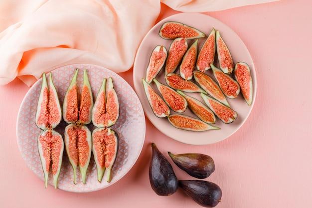 Инжир в тарелках плоско уложить на розовый и текстиль