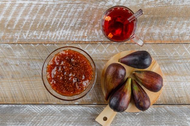 Инжир с чашкой чая, вид сверху варенье из инжира на деревянной и разделочной доске