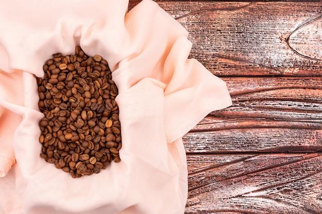 木製の表面に布でトップビューコーヒー豆