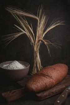 Мука в миске с пшеницей и хлебом, вид сбоку на темно-коричневый