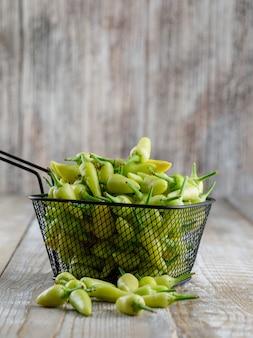 Зеленые перцы в дуршлаге на деревянном, взгляде со стороны.