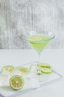 Лимонад в стакане с лимоном, разделочная доска, кубики льда, вид сбоку на белый и шероховатый