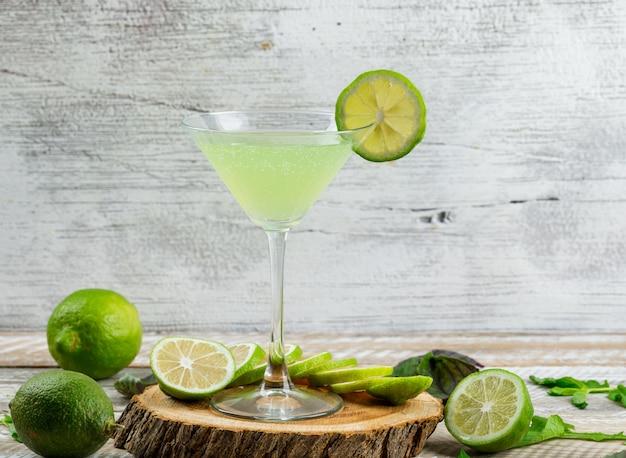 Лимонад в стакане с лимонами, листьями, разделочная доска, вид сбоку на деревянные и шероховатый
