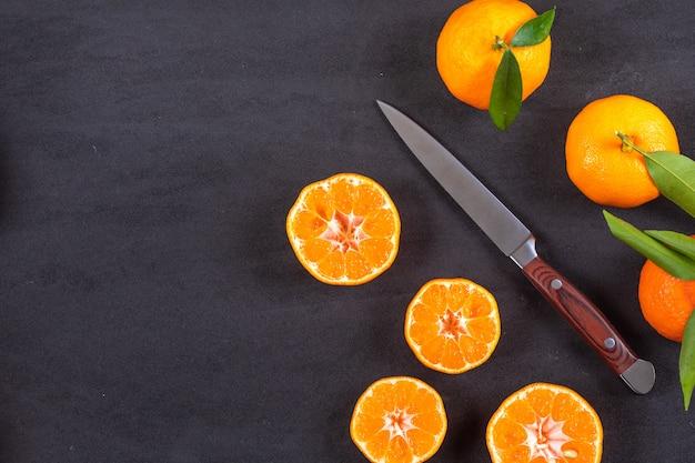 Вид сверху мандарины с ножом на черной поверхности