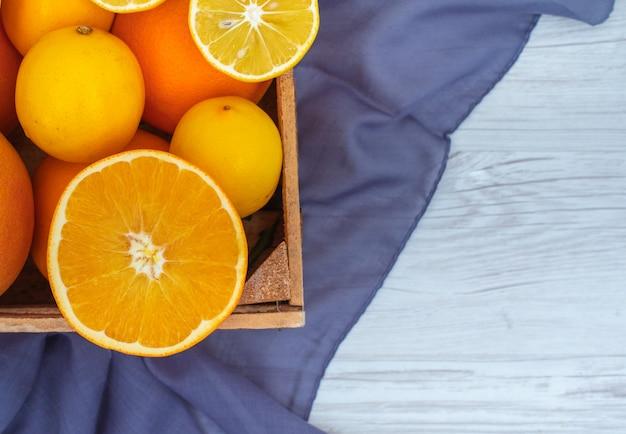 Вид сверху апельсин и лимон в деревянной корзине над цветной тканью