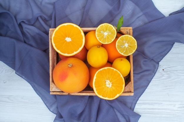 Вид сверху оранжевые фрукты в деревянной коробке на синей ткани